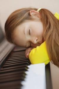 little girl in yellow dress asleep on piano